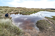 A pond in the middle of the dunes by Bamburgh Castle is seen reflecting the sky on Wednesday, March 17, 2021. Bamburgh is home to the most important Anglo-Saxon archaeological sites in the world, the Bamburgh Castle. (Photo/ Vudi Xhymshiti)