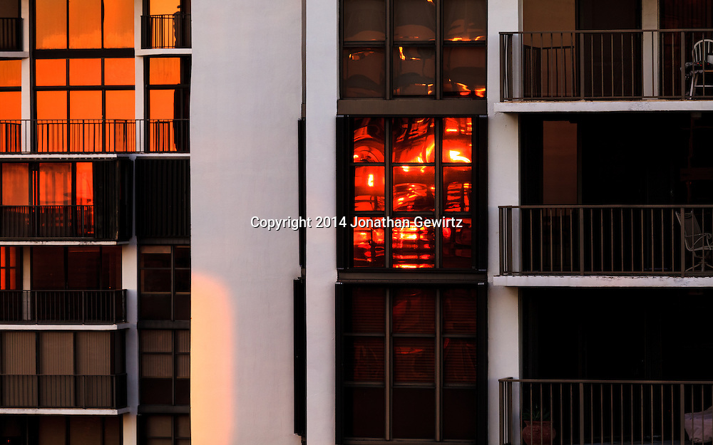 Windows in a high rise apartment building reflect reddish light from the setting sun.<br /> <br /> WATERMARKS WILL NOT APPEAR ON PRINTS OR LICENSED IMAGES.
