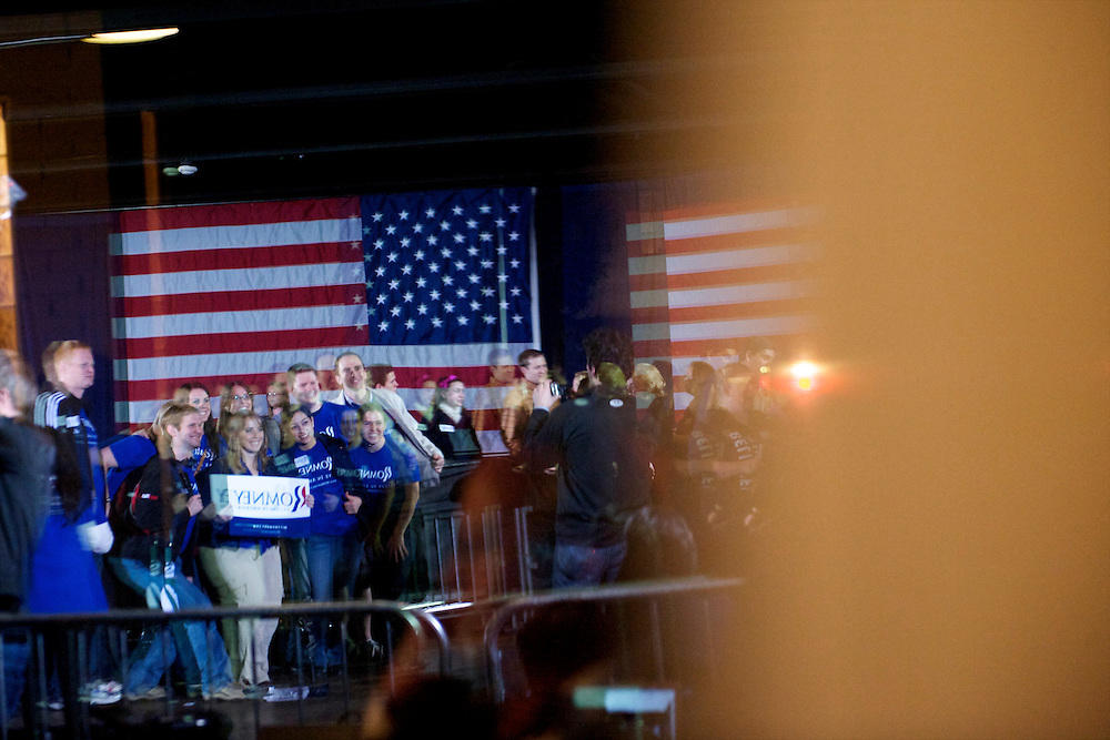 A reflection of a group of supporters pose for photos in front of the stage where Republican Presidential candidate Mitt Romney held a rally at Saw Mill at Larkin's on the eve of the South Carolina primary