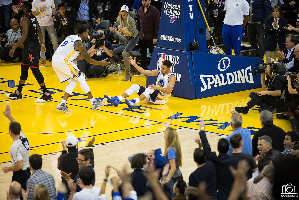 Golden State Warriors forward Andre Iguodala (9) helps guard Stephen Curry (30) up off the floor after scoring a lay up against the Houston Rockets at Oracle Arena in Oakland, Calif., on December 1, 2016. (Stan Olszewski/Special to S.F. Examiner)