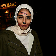 A lady wearing hijab with Halloween face painting a night in Westend on 31 October 2018, London, UK.