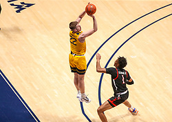Jan 25, 2021; Morgantown, West Virginia, USA; West Virginia Mountaineers guard Sean McNeil (22) shoots a three pointer from the corner over Texas Tech Red Raiders guard Terrence Shannon Jr. (1) during the second half at WVU Coliseum. Mandatory Credit: Ben Queen-USA TODAY Sports