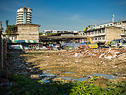 29 SEPTEMBER 2015 - BANGKOK, THAILAND:  A BTS Skytrain passes land being cleared for redevelopment with Bang Chak Market in the background. The Bang Chak Market serves the community around Sois 91-97 on Sukhumvit Road in the Bangkok suburbs. About half of the market has been torn down, vendors in the remaining part of the market said they expect to be evicted by the end of the year. The old market, and many of the small working class shophouses and apartments near the market are being being torn down. People who live in the area said condominiums are being built on the land.       PHOTO BY JACK KURTZ