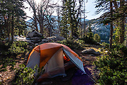 """Sunrise hits our tent at Big Sandy Lake Campground in Bridger Wilderness, Wind River Range, Bridger-Teton National Forest, Rocky Mountains, Wyoming, USA.  Backpack to Big Sandy Lake Campground (11 miles round trip with 1000 feet gain). Day hike from Big Sandy Lake to Clear Lake and Deep Lake below East Temple Peak then loop back via Temple Lake, Miller Lake, and Rapid Lake (7.5 miles, 1060 ft gain) on the Continental Divide Trail. The Continental Divide follows the crest of the """"Winds"""". Mostly composed of granite batholiths formed deep within the earth over 1 billion years ago, the Wind River Range is one of the oldest mountain ranges in North America. These granite monoliths were uplifted, exposed by erosion, then carved by glaciers 500,000 years ago to form cirques and U-shaped valleys. Glaci"""