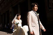 Chinese bride walks behind her new husband dusing photoshoot walk in Florence's Piazza degli Uffizi.