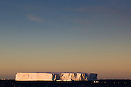A tabular iceberg floats nearby as the ship crosses the Antarctic Circle (near Adelaide Island) at dusk.