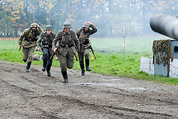 World War Two Re-enactors portraying panzer grenadiers carrying K98 Rifles run to take up positions during a battle battle re-enactment in on Pickering Showground<br /> <br /> 17/18 October 2015<br />  Image © Paul David Drabble <br />  www.pauldaviddrabble.co.uk