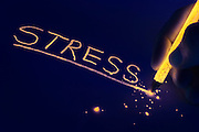"""A glowing pencil tip shatters after underlining the word """"stress"""".Black light"""