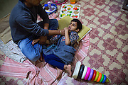Rachi, 7, a disabled girl affected by microcephaly and myoclonic epilepsy, is receiving speech therapy while laying on the floor of 'Chingari Trust Rehabilitation Centre', one of two vital medical institutions funded by 'The Bhopal Medical Appeal' in Bhopal, Madhya Pradesh, central India.