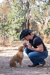cowboy with a puppy outdoors