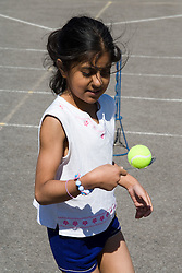 Girl taking part in sports day competition in school playground,