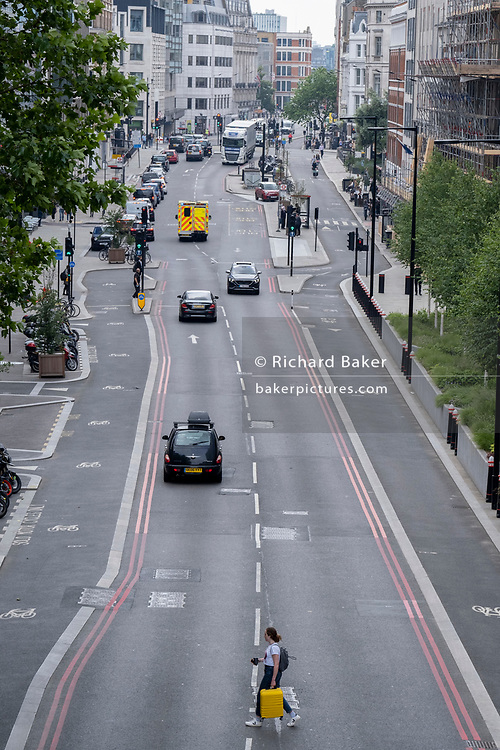 A lone woman carrying a yellow suitcase, crosses the Farringdon Road in the City of London, the capital's financial district, on 24th June 2021, in London, England. CREDIT RICHARD BAKER.