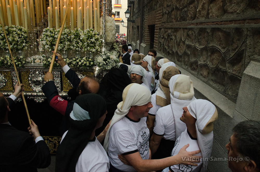 Costaleros of the brotherhood 'Los Estudiantes' replacing other 'costaleros' of the virgin's float at Cordon Street in Madrid.