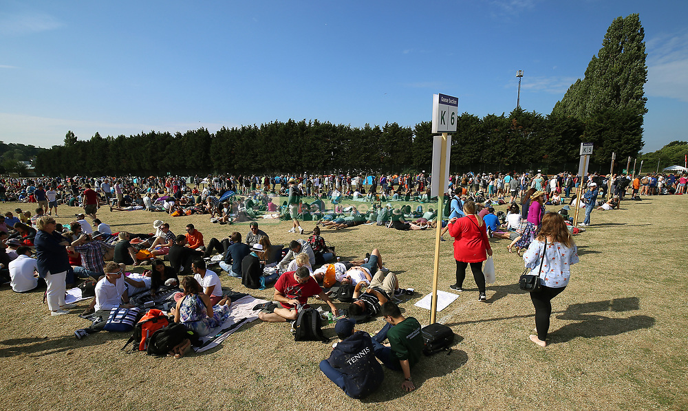 Spectators relax in the queue at the start of day three of the Wimbledon Championships at the All England Lawn Tennis and Croquet Club, Wimbledon.