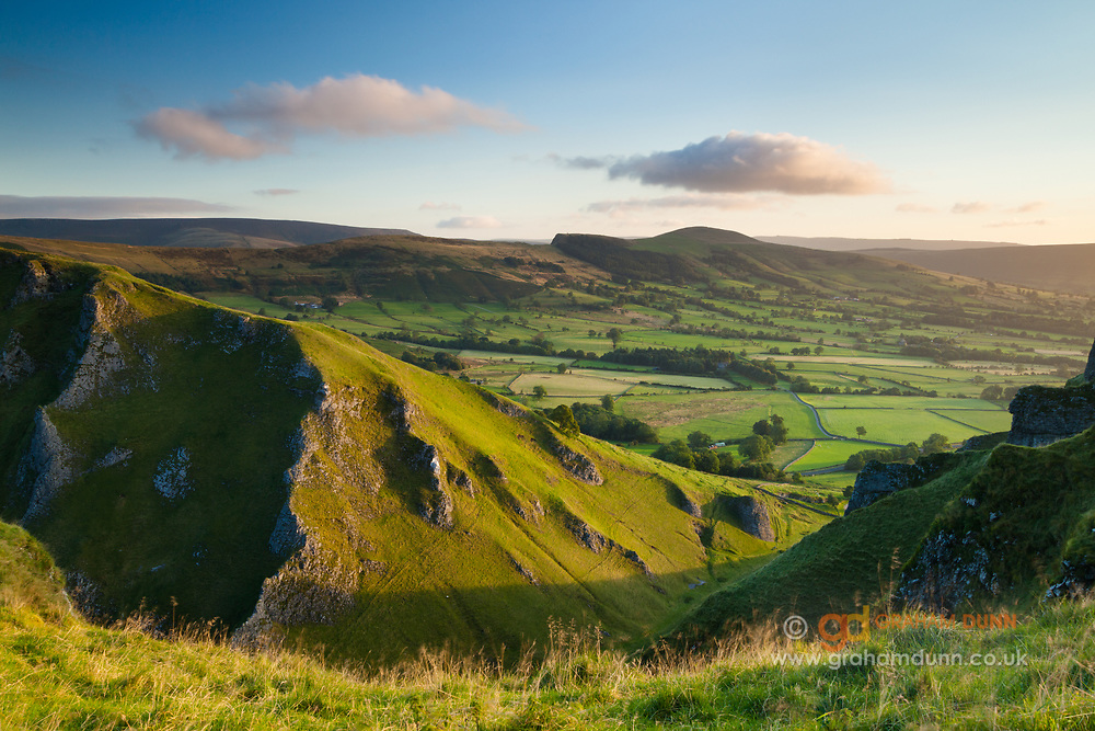 The steep limestone cliffs of Winnats Pass looking onto the Hope Valley and a distant Lose Hill. A sunrise landscape scene in the Derbyshire Peak District. England, UK.