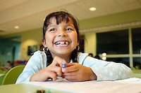 Viviana Reyes, 7, takes a smile break from her homework after school at the César Chávez Library in Salinas