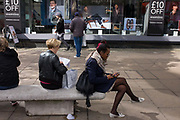 A woman sits with legs crossed in front the Debenhams exterior featuring a male model echoing the same sitting position. Shoppers are on the busy Oxford Street in the capital, a location for many high and low-end shops and stores. Londoners sit on stone benches to rest and gather themselves, to check messages and inspect their purchases. In the background we see the same male model wearing various clothing on sale inside this shop.