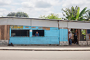 """Junto a las vías del tren en Tenosique, Tabasco, pueden encontrarse casas donde se rentan cuartos y baños, agua gratuita, o se ofrece intercambio de moneda. Estos lugares suelen ser usados por enganchadores para negociar el viaje con los """"polleros"""". (Foto: Prometeo Lucero)"""