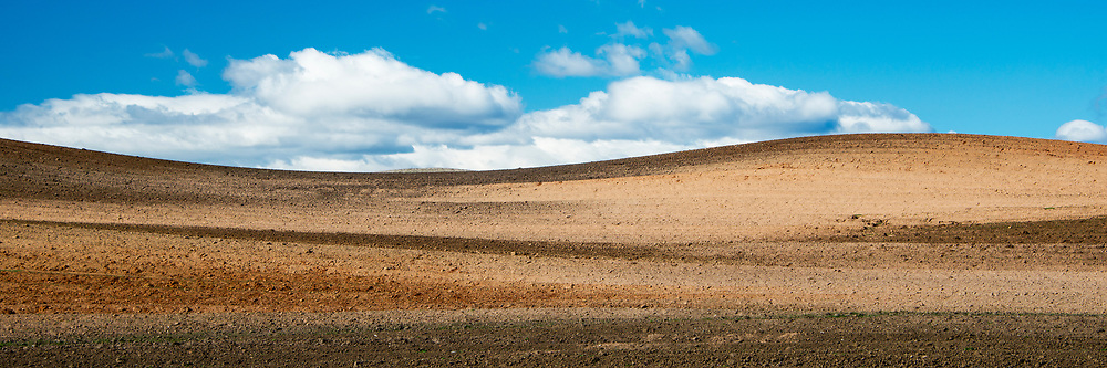 Blue sky with stratus clouds peeking over a rolling hill that has been tilled for planting. Woodland, California.
