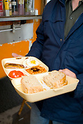 A man holding a takeaway all day breakfast in a polystyrene container on the 21st June 2008 in Victoria in the United Kingdom.