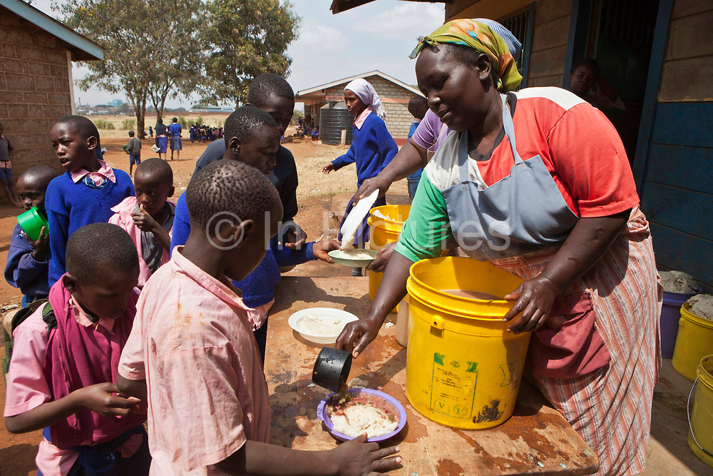 Florence serves out the lunch at Graissa Road Primary School. Her wages are paid by AFCIC (Action for children in conflict). The majority of the pupils are from the Kiandutu slum. The school has 800 children.