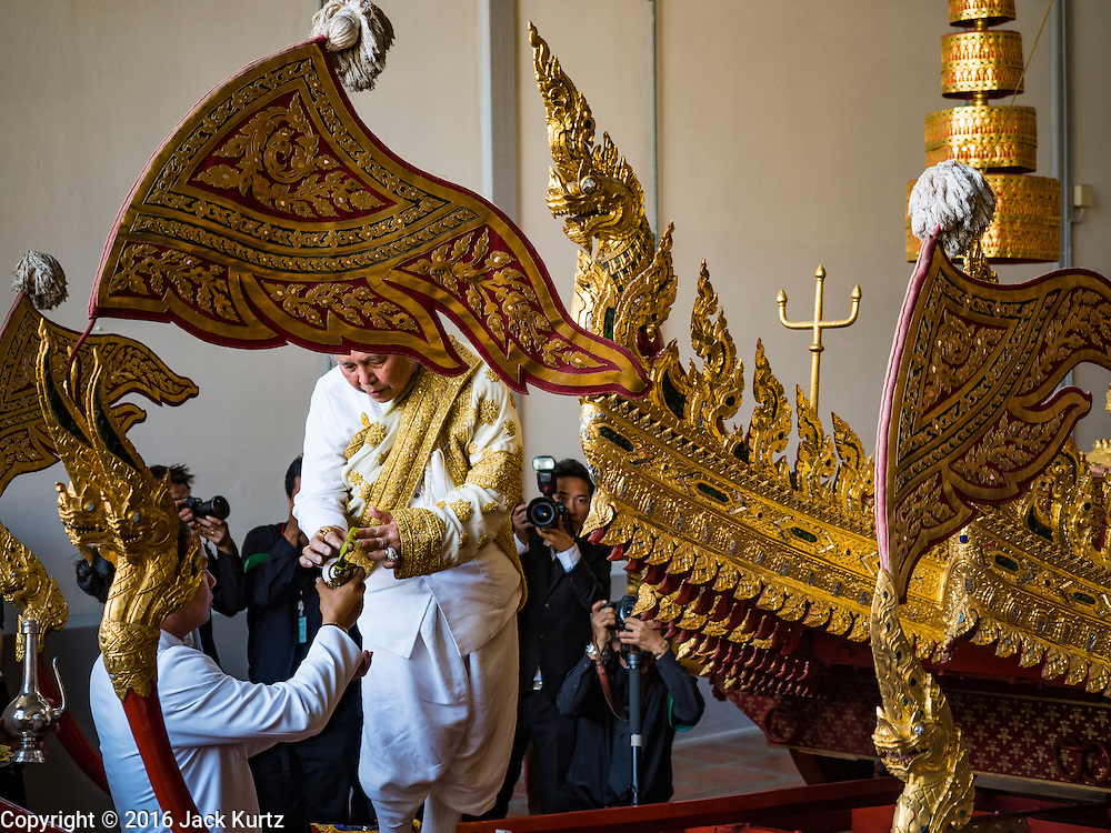 """19 DECEMBER 2016 - BANGKOK, THAILAND:  PHRA MAHA RAJA GURU BIDHI SRI VISUDHIGUN, head Brahmin in the Royal Ceremonial Affairs Division, blesses a chariot during the """"Spirit Appeasing"""" Ceremony for the Royal Chariots at the Bangkok National Museum. The chariots will be used to take the body of Bhumibol Adulyadej, the Late King of Thailand, and members of the Royal funeral cortege to the cremation site on Sanam Luang for His Majesty's cremation. This will be the first cremation of a Thai King since 1950, when King Bumibol's brother, Rama VIII, Ananda Mahidol, was cremated. The design of the royal crematorium is based on Buddhist cosmology, with the main peak of Mount Sumeru (also known as Meru in Hindu cosmology) at center and eight other peaks signifying the levels of the universe. The crematorium will be decorated with mythical creatures such as garuda, angels, and Himmapan Forest creatures. The structure and funeral pyre will stand just over 50 meters tall. The exact date of the King's cremation has not been set yet but is expected to be late next year.    PHOTO BY JACK KURTZ"""