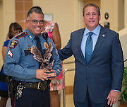 Corporal Gilbert Garcia, left, receives the Eagle Award from Chief Robert Mock, right, during the Houston ISD Police awards banquet at Thompson Elementary School, August 15, 2014.