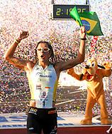 Adriano Bastos, left, of Brazil, celebrates with Goofy after winning the Walt Disney World Marathon in Lake Buena Vista, Florida.