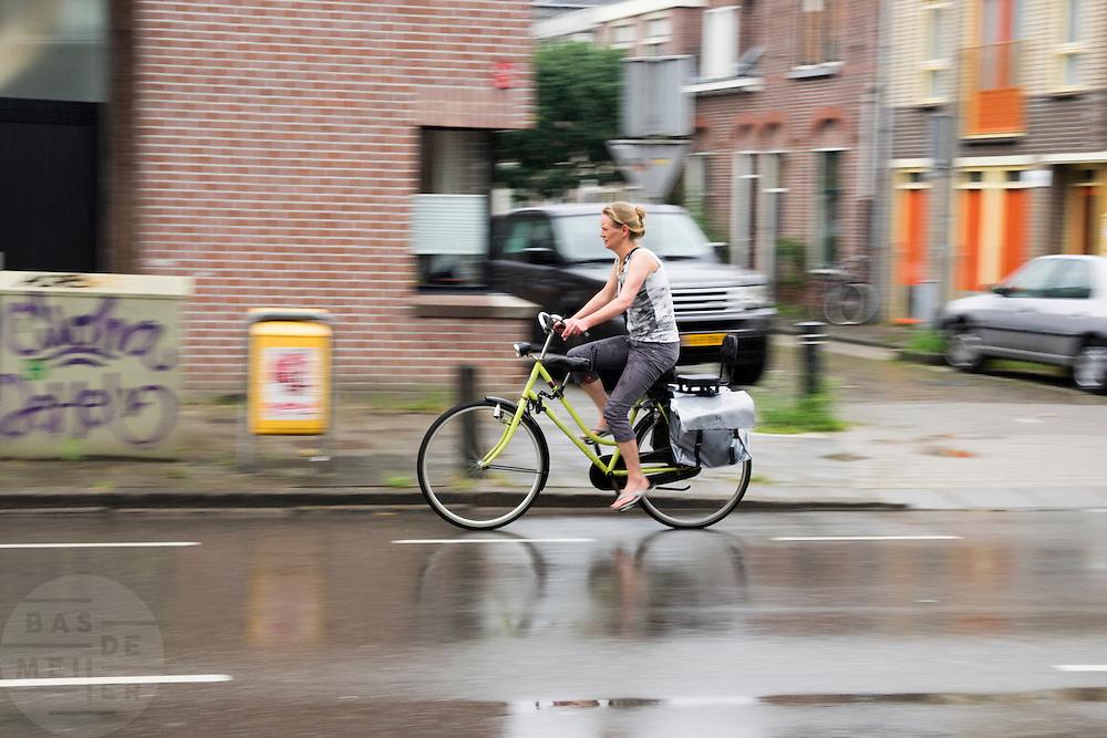 In Utrecht rijdt een vrouw op de fiets door de regen.<br /> <br /> In Utrecht cyclists a woman cycles in the rain.
