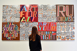 "© Licensed to London News Pictures. 04/09/2018. LONDON, UK.  A staff member views ""The Secret of a Good Life"", by celebrated artist Bob and Roberta Smith RA, the first display by a Royal Academician in the new Ronald and Rita McAulay Gallery, a new space dedicated to site-specific installations by Royal Academicians in the new Royal Academy in Piccadilly.  This and other works are on display 4 September to 3 February 2019.  Photo credit: Stephen Chung/LNP"