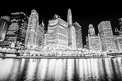Chicago at night black and white photo. Includes buildings along the Chicago River between Dusable Bridge (Michigan Avenue Bridge) and Irv Kupcinet Bridge (Wabash Avenue Bridge) facing South. Buildings include London Guarantee Building / Crain Communications Building (360 North Michigan) Mather Tower (75 East Wacker Drive), Hotel 71 Building, 35 East Wacker Drive Building, Unitrin Building (1 East Wacker Drive), Renaissance Chicago Hotel.