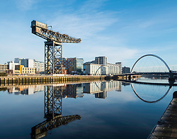 View of Finnieston Crane beside River Clyde on blue sky winter day, Scotland, United Kingdom