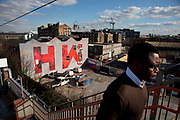 Large scale letters covering a promotional mural spell out 'H W' standing for 'Hackney Wick' Street art in the East End of London is an ever changing visual enigma, as the artworks constantly change, as councils clean some walls or new works go up in place of others. While some consider this vandalism or graffiti, these artworks are very popular among local people and visitors alike, as a sense of poignancy remains in the work, many of which have subtle messages.