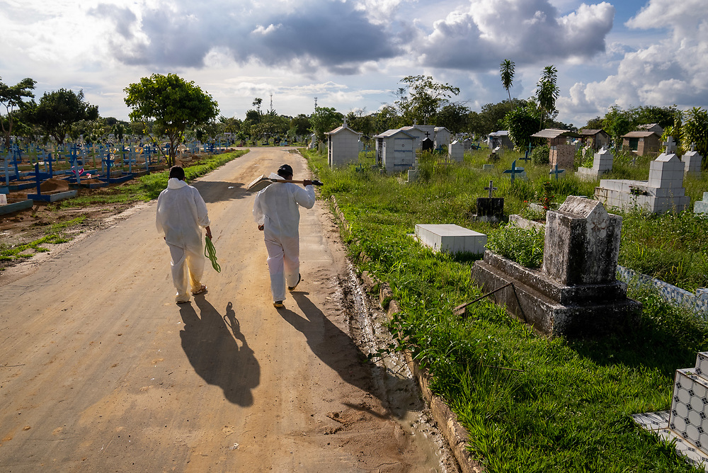 Grave diggers walk down a road at Nossa Senhora Aparecida public cemetery March 30, 2021 in Manaus, Brazil. The majority of their work is for people who died of Covid. Brazilian residences are receiving the CoronaVac vaccine, also known as the Sinovac COVID-19 vaccine. CoronaVac is an inactivated virus COVID-19 vaccine developed by the Chinese company Sinovac Biotech and has been in Brazil's Phase III clinical trials. Photo Ken Cedeno