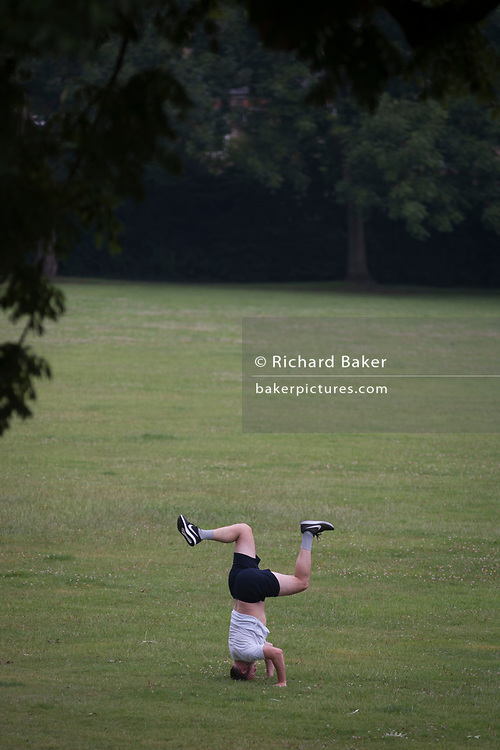 An upside down man remains balanced on his head in a public park - one in a sequence of four - on 19th July 2017, in Ruskin Park, south London borough of Lambeth, England.