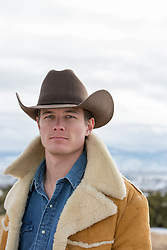 portrait of a handsome cowboy in a shearling coat