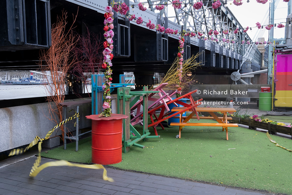 As hazard tape blue in the breeze, stacked outdoor cafe benches remain un-used on the Southbank during the third lockdown of the Coronavirus pandemic, on 11th March 2021, in London, England.