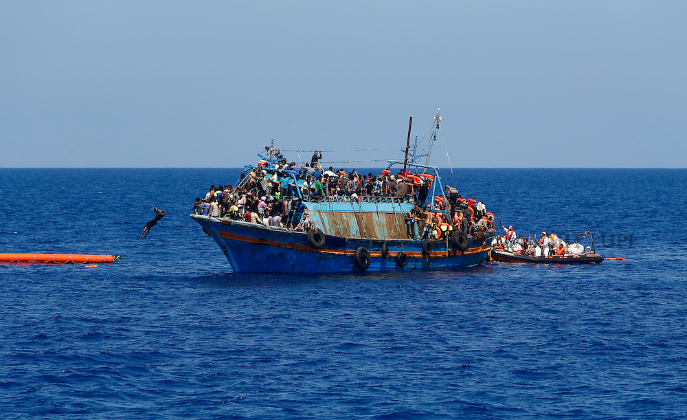 A migrant dives into the water from an overloaded wooden boat during a rescue operation off the coast of Libya August 6, 2015.  An estimated 600 migrants on the boat were rescued by the international non-governmental organisations Medecins san Frontiere (MSF) and the Migrant Offshore Aid Station (MOAS) without loss of life on Thursday afternoon, a day after more than 200 migrants are feared to have drowned in the latest Mediterranean boat tragedy after rescuers saved over 370 people from a capsized boat thought to be carrying 600.<br /> REUTERS/Darrin Zammit Lupi <br /> MALTA OUT. NO COMMERCIAL OR EDITORIAL SALES IN MALTA