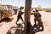 12 JUNE 2006 - SAN LUIS, AZ: National Guardsmen hold up a fence while another soldier works on it in San Luis, AZ. Mexico is a few feet behind the soldiers on the right. Fifty five members of the 116th Engineer Company, Combat Support Engineers, of the Utah Army National Guard are in San Luis, AZ, to build a fence and improve roads east of the San Luis Port of Entry on the US/Mexico border. The unit is the first of an estimated 6,000 US military personnel, almost all of them Army National Guard, who will be dispatched to the US/Mexico border by President Bush to help control immigration on the border. The Guardsmen will primarily build roads and fence and staff surveillance centers. They will not be engaged in first line law enforcement work.  Photo by Jack Kurtz