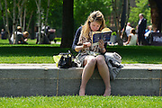 © Licensed to London News Pictures. 31/05/2013. London, UK A woman reads and eats her lunch outside in the sunshine.  Children and office workers enjoy the hot weather near to City Hall and Tower Bridge in London today May 31st 2013. Photo credit : Stephen Simpson/LNP