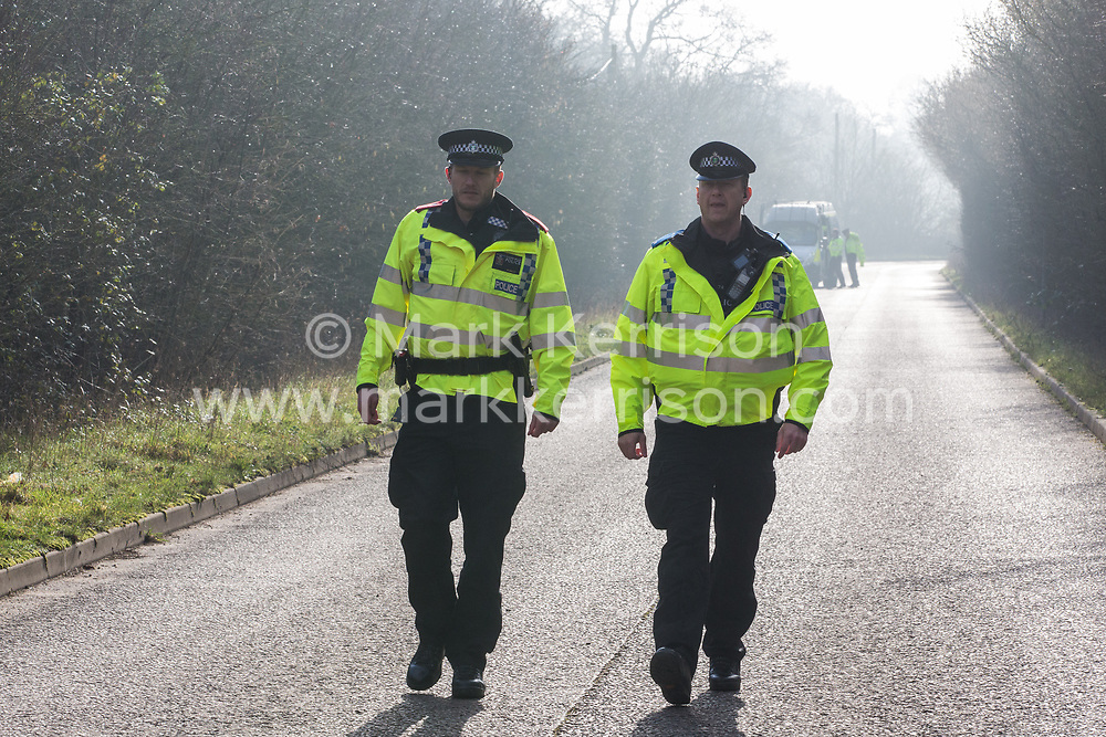 Denham, UK. 6 February, 2020. Senior police officers arrive to attempt to move on environmental activists from Save the Colne Valley, Stop HS2 and Extinction Rebellion walking at a snail's pace along a road so as to block for several hours a security vehicle and truck delivering fencing and other supplies to be used for works associated with the HS2 high-speed rail link close to the river Colne at Denham Ford. Some activists also collected litter during the action.