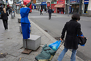 Local shoppers walk past a blue dress from a nearby street market ladieswear stall, on 8th October 2019, in Barking, Essex, England.