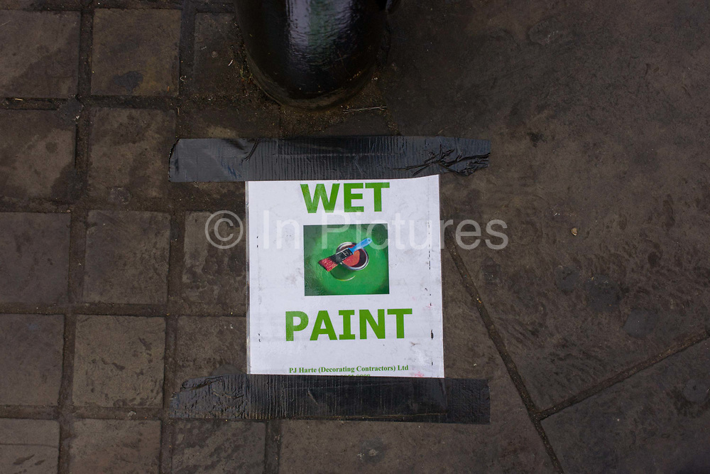 Warning of Wet Paint, taped to the pavement in a central London sidestreet. The contractor has printed the notice and stuck it to the ground using gaffer tape. The warning is meant to be seen and taken seriously so green is the theme of this sign - a paint brush with red paint in a circle of green: Two prime colours to attract the unwary.