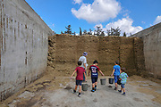 Bales of straw in storage in a dairy farm. Photographed at Kibbutz Harduf, Galilee, Israel. Children sent to collect the straw
