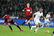 Andre Ayew of Swansea city ® breaks away from Claudio Yacob of West Bromwich Albion (l). Barclays Premier league match, Swansea city v West Bromwich Albion at the Liberty Stadium in Swansea, South Wales  on Boxing Day Saturday 26th December 2015.<br /> pic by  Andrew Orchard, Andrew Orchard sports photography.