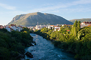 The Neretva River in Mostar, Bosnia and Herzegovina.  The spire is part of the Franciscan church.