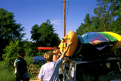 Stock photo of men loading kayaks onto the top of a car for transport