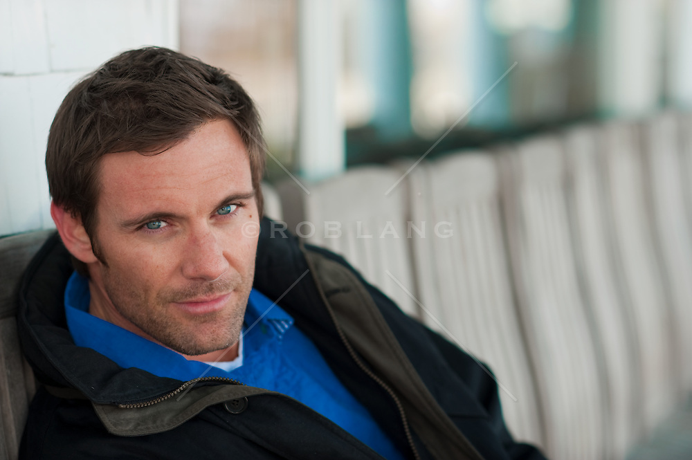 man with blue eyes and brown hair on a chair outdoors