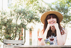Beautiful woman with wine glasses and grapes on outdoor restaurant
