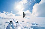 Alaska, Chugach State Park. Backcountry skiers climb snow-covered peak near Eagle River.
